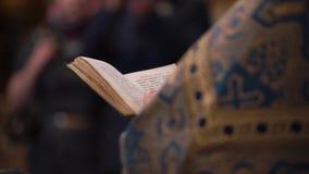 Padre que reza com o livro da Bíblia na igreja filme