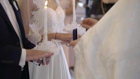 Padre que rezam na igreja na cerimônia de casamento e anéis sobre postos para recém-casados filme