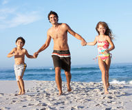 Padre que se ejecuta con los niños a lo largo de la playa de Sandy Fotografía de archivo libre de regalías