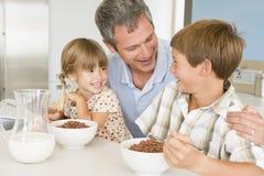 Padre que se sienta con los niños como comen el desayuno Fotos de archivo