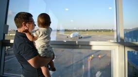 Padre que sostiene su aeroplano del bebé en fondo metrajes
