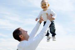 Padre que sostiene su sol contra el cielo Foto de archivo