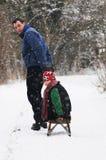 Padre que tira del hijo en el trineo Imagen de archivo libre de regalías