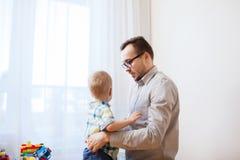 Padre que toma cuidado del pequeño hijo en casa Fotos de archivo