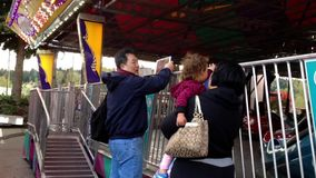 Padre que toma la imagen para la familia que juega los coches de parachoques almacen de video
