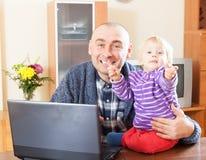 Padre que trabaja con el bebé Foto de archivo libre de regalías