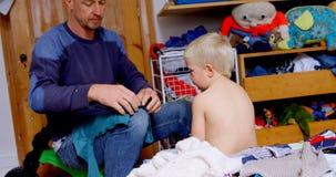 Padre que viste para arriba a su hijo en el dormitorio en casa 4k almacen de metraje de vídeo
