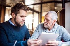 Padre senior e giovane figlio con la compressa in un caffè Fotografia Stock Libera da Diritti