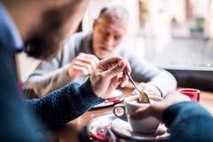 Padre senior ed il suo giovane figlio in un caffè Fotografie Stock