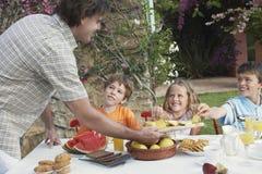 Padre Serving Pineapple Slices a los niños en la tabla al aire libre Foto de archivo