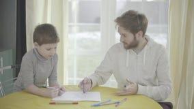 Padre smilling barbuto e la sua piccola pittura del figlio su carta che si siede nel salone alla tavola relazione del Padre-bambi archivi video