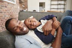 Padre And Son Cuddling en Sofa Together foto de archivo