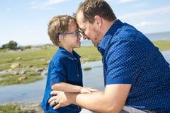 Padre And Son Hugging en verano al aire libre foto de archivo libre de regalías