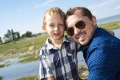 Padre And Son Hugging en verano al aire libre fotografía de archivo