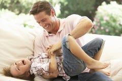 Padre With Son Laughing insieme sul sofà Fotografia Stock