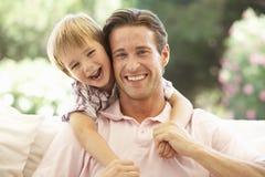 Padre With Son Laughing junto en el sofá Foto de archivo