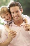 Padre With Son Laughing junto en el sofá Fotografía de archivo