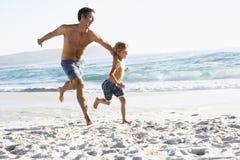 Padre And Son Running a lo largo de la playa juntos que lleva los trajes de natación Imágenes de archivo libres de regalías