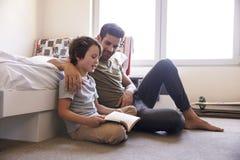 Padre And Son Siting sul libro di lettura del pavimento della camera da letto insieme Immagine Stock