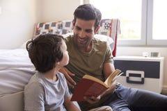 Padre And Son Siting sul libro di lettura del pavimento della camera da letto insieme Fotografie Stock Libere da Diritti