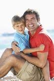 Padre And Son Sitting en la playa junto Imagen de archivo libre de regalías