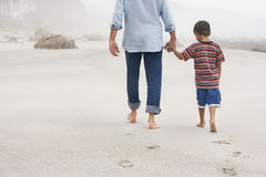 Padre And Son Walking en la arena en la playa fotografía de archivo