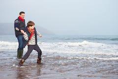 Padre And Son Walking en la playa del invierno y piedras que lanzan Foto de archivo libre de regalías