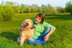 Padre sonriente con el perro que se sienta en la tierra en parque Imagenes de archivo