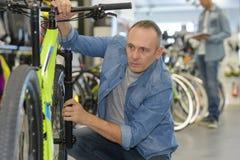 Padre sonriente feliz que elige la nueva bici del deporte en tienda Imagen de archivo libre de regalías