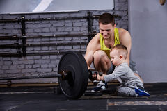 Padre sonriente joven y pequeño hijo lindo con pesas de gimnasia contra la pared de ladrillo en el gimnasio apto de la cruz fotos de archivo