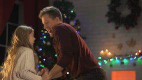 Padre sonriente que cosquillea a la pequeña hija adorable el la víspera de Navidad, disfrutando de día de fiesta almacen de metraje de vídeo