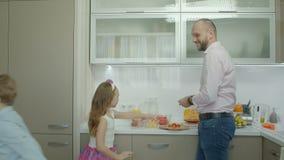 Padre sonriente que hace el desayuno en cocina almacen de video