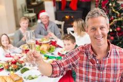 Padre sonriente que tuesta en la cámara delante de su familia Fotos de archivo libres de regalías