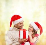 Padre sorridente che dà il contenitore di regalo della figlia immagine stock