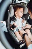 Padre sorridente che mette bambino nel sedile del bambino, cintura di sicurezza di fissaggio - trasporto della famiglia, concetto fotografie stock