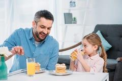 padre sorridente e piccola figlia che mangiano prima colazione fotografia stock