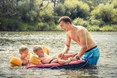 Padre sorridente felice che gioca i figli dei bambini che nuotano paternità ed infanzia felici di concetto del ritratto di stile  fotografia stock libera da diritti