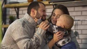 Padre sorridente in maglione caldo che gioca con il piccolo figlio del bambino che è in armi della madre nella cucina Bambino che archivi video