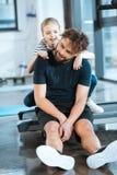 Padre stanco di abbraccio della ragazza che si siede dopo l'allenamento sulla pedana mobile Immagini Stock