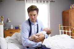 Padre subrayado Dressed For Work que detiene al bebé en dormitorio Fotos de archivo libres de regalías
