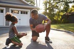 Padre Teaching Son How para jugar a baloncesto en la calzada en casa imagen de archivo