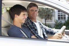 Padre Teaching Teenage Son a conducir Imagen de archivo libre de regalías