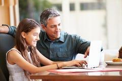 Padre And Teenage Daughter que mira el ordenador portátil junto Imágenes de archivo libres de regalías