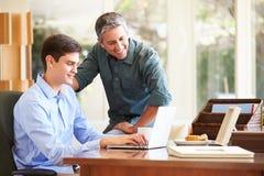 Padre And Teenage Son que mira el ordenador portátil junto Imágenes de archivo libres de regalías