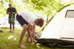 Padre And Teenage Son que pone encima de la tienda en acampada Imagenes de archivo