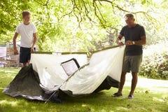 Padre And Teenage Son que pone encima de la tienda en acampada Imagen de archivo libre de regalías