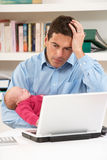 Padre tensionado con el bebé que trabaja de hogar Foto de archivo