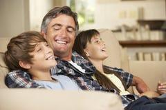 Padre And Two Children que se sienta en Sofa At Home Watching TV junto Imagen de archivo