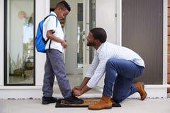 Padre Tying Sons Shoelaces como él se va para la escuela imagen de archivo libre de regalías