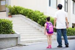 Padre Walking To School con los niños Imagen de archivo libre de regalías